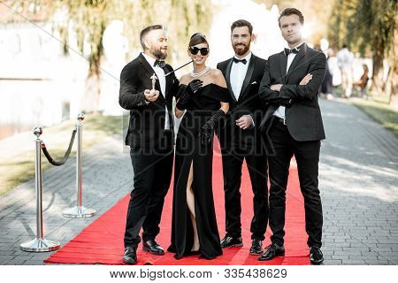 Group Portrait Of An Elegant People As A Famous Movie Actors Standing Together On The Red Carpet Dur