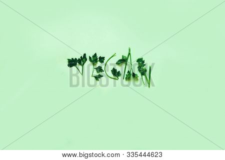 The Word Vegan Laid Out By Greens On A Background Of Lettuce Leaves. Fresh Raw Parsley On Mint Color