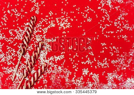 Christmas Lollypops On A Red Sparkle Background. Festive Mood, Luxury Party, Winter Holidays, Sweets