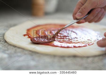 cook puts ingredients on pizza