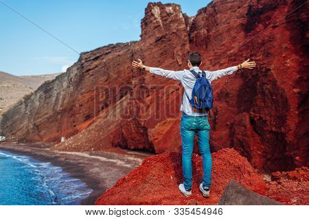 Traveler Looking At Red Beach Landscape With Arms Raised Feeling Happy In Akrotiri, Santorini Island