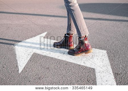 Feet Walking Along The Left Turn Sign. Concept Of Making Correct Decisions, Changing Direction Or At