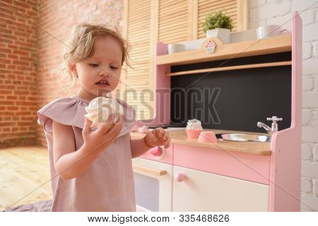 Children And Unhealthy Sugary Food. Cute Little Girl In Linen Dress Eating Big Meringue In Light Pla