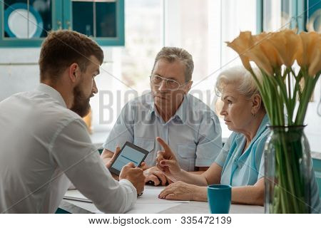 Senior Couple Discussing With Financial Advisor At Home