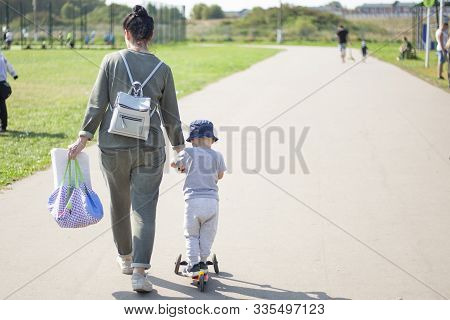 Walk With A Child In The Park. A Woman Leads A Child. Boy Learn To Ride A Scooter. Rest In The Park.