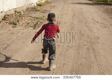 Naughty Child Running Along A Dusty Road.
