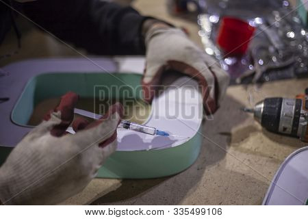 Syringe Glue Is Poured Into The Bonding Material. Creating A Letter For An Advertising Sign In A Wor