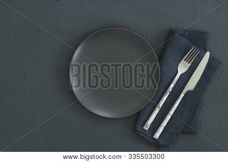 Empty Black Slate Plate On Dark Stone Table And Napkin. Food Background For Menu, Recipe. Table Sett