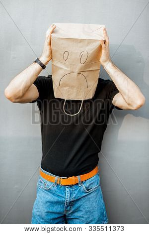 Portrait Of A Disappointed Man With Paper Bag On His Head Standing On The Grey Background. Concept O