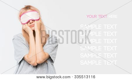 Close Up Studio Portrait Of Sleepy Young Girl In Grey T-shirt. Drowsy Woman Girl Rubs Her Eyes Under