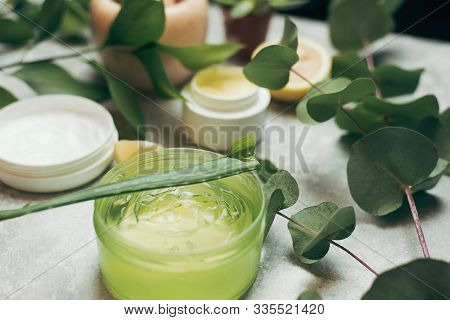 A Can Of Aloe Gel Next To An Aloe Branch And Eucalyptus Leaves. Green Aloe Gel On A Background Of Na