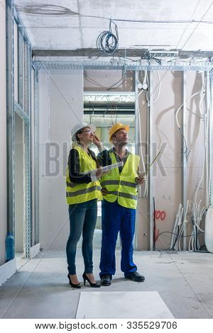 Construction worker and architect discussing work to be done at site to finish the building