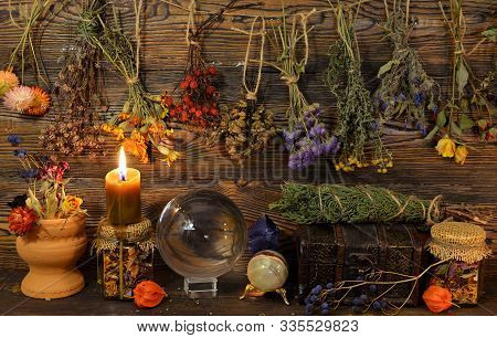 Still Life With Dry Herbs, Crystal Ball, Bottle And Burning Candle On Witch Table. Esoteric, Wicca A