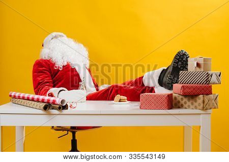 Santa Claus Also Needs An Ocasional Break. Hes Working At The Desk.