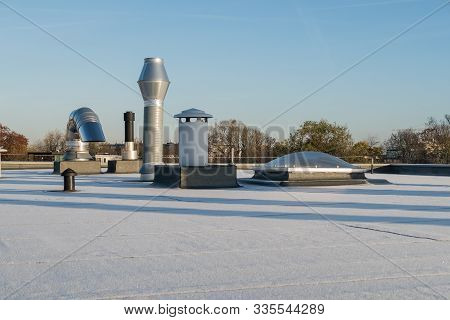 Chimney On The Flat Roof Off A Big Building In The City