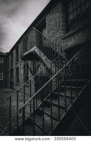 Outside Metal Staircase Of A Desolate Brick Building. Concept Of Desolation, Silence And Being Locke