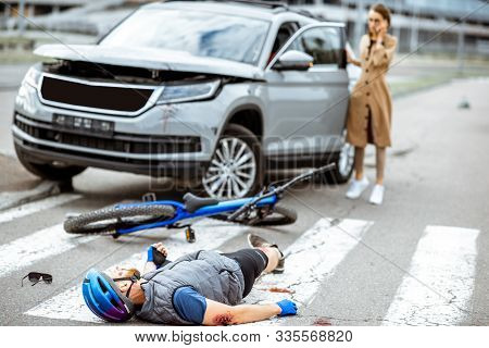 Road Accident With Injured Cyclist Lying On The Pedestrian Crossing Near The Broken Bicycle And Worr