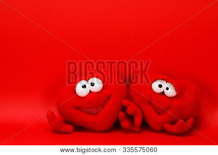 Two wool red hearts on red background with copy space for text, symbol of love, healtcare, valentines day concept