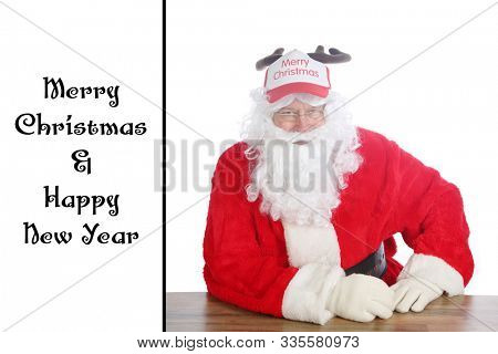 Santa Claus wears a Reindeer Antler Hat. Santa sits and models his Ball hat complete with antlers. Isolated on white with room for text. Merry Christmas and Happy New Year. Text is easily replaced.