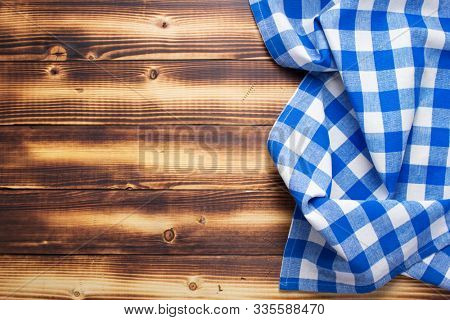 checked cloth napkin or tablecloth at rustic wooden plank board table background, top view