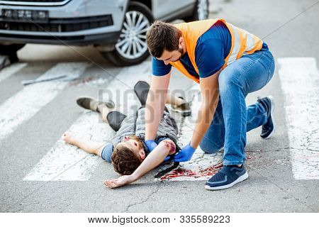 Man Applying First Aid To The Injured Bleeding Person, Wearing Tourniquet On The Arm After The Road
