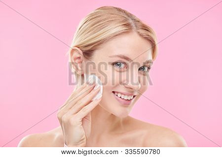 Pretty young smiling female with cotton pad applying toner or micellar water while cleansing her face against pink background