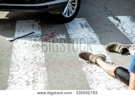 Scene Of A Road Accident With Car, Broken Parts And Injured Man Lying On The Pedestrian Crossing