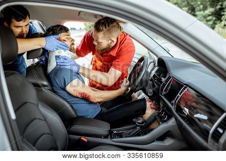 Medics Wearing Neck Corset To An Injured Man Sitting In The Car After The Road Accident, Providing E