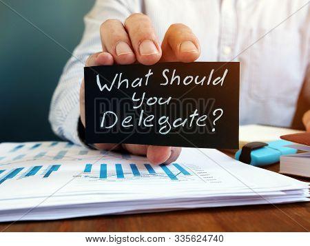 Businessman Holds Sign What Should You Delegate. Delegation Concept.