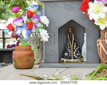 Scene In A Cemetery: In The Chapel Of A Tomb, An Image Of Our Lady Of Aparecida, Patroness Of Brazil