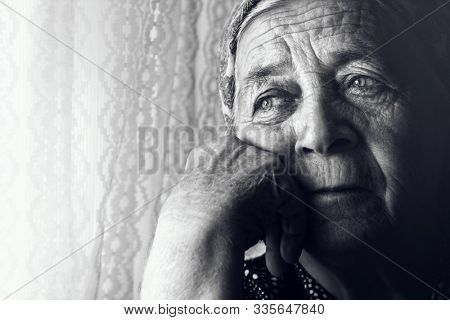 Black and white portrait of depressed sad old woman