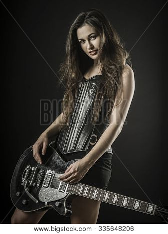 Photo Of A Beautiful Young Sexy Woman Holding An Electric Guitar Over Black Background.