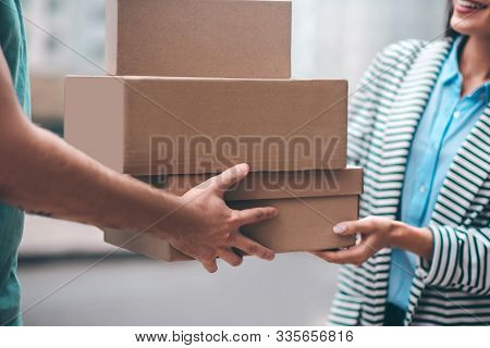 Close Up Of Delivery Man Passing Boxes With Order To The Customer