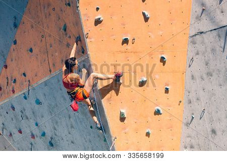 Training At The City Climbing Gym. A Strong Woman Climbs A Climbing Route On Artificial Terrain. Sli