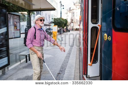 Senior Blind Man With White Cane Getting On Public Transport In City.