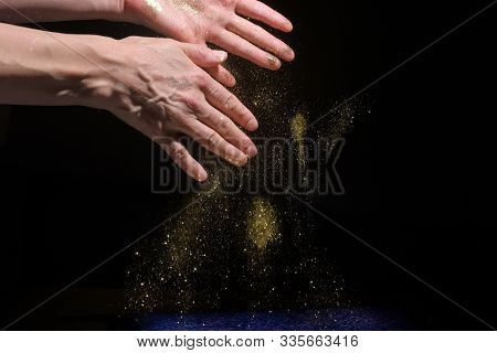 Woman Hands Drop Glitter Sparkles On Black Background