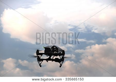 A Black Quadcopter With A Digital Camera Flies In A Cloudy Sky. Unmanned Aerial With Propellers Agai