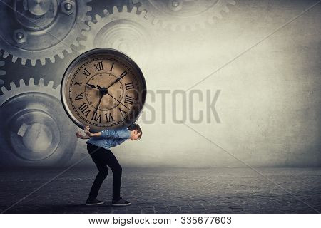 Bent Down Guy Carrying A Big Heavy Clock On His Back. Overloaded Student Tired Of Daily Tasks, And D