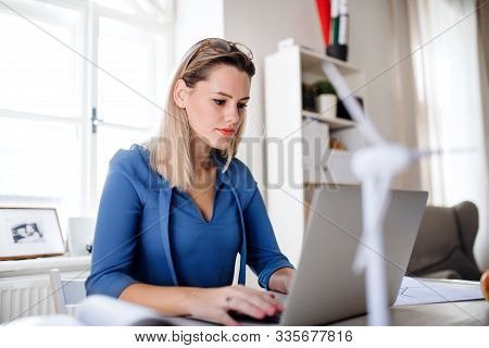 Young Woman With Laptop Sitting At The Desk Indoors In Home Office, Working.