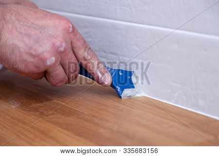 Closeup Hands Of Professional Plumber Worker Applying White Sealant, Joint Compound, Caulk To Joint