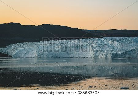 Greenland Glacier Nature Landscape With Famous Eqi Glacier And Lodge Cabins. Midnight Sun And Pink S