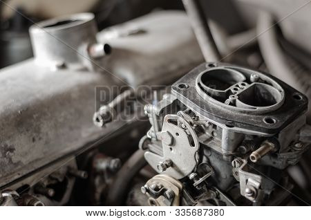 Engine Compartment Of An Old Car. Close-up View Of A Gasoline Carburetor Against A Background Of A C