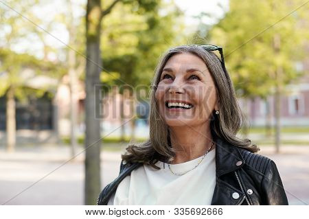 Cheerful Beautiful Mature Woman In Her Fifty Enjoying The Nice Summer Weather Outdoors In The Park,
