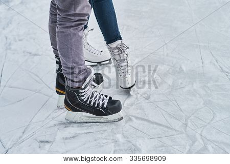 Young Loving Couple Skating At Ice Rink Outdoors, Close-up View Of The Skates