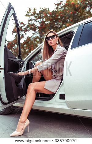 Stylish Fashionable Beautiful Woman Enters From Interior Of White Car, Business Class Sedan. Taxi, C