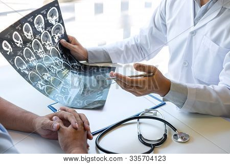 Doctor Holding And Looking At X-ray Film Examining At Brain By Ct Scan Of Patient And Analyze Result