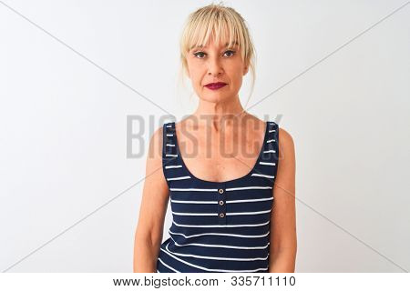 Middle age woman wearing casual striped t-shirt standing over isolated white background with serious expression on face. Simple and natural looking at the camera.