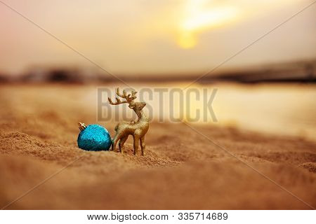 Christmas Decoration In The Form Of A Golden Deer And A Ball On The Beach During A Beautiful Sunset.