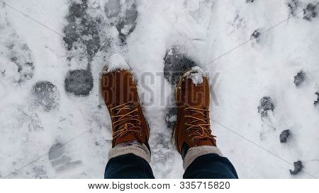 Bright Yellow Boots In Wet, Dirty Snow. Weather Forecast. Bad Weather Concept.