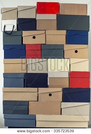 Pile Of Evenly Folded Shoe Boxes Against A White Wall. Seasonal Sales And Discounts. Vertical Photo.